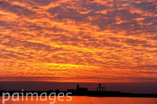 A general view of the sunrise over the Sean Henry sculpture entitled COUPLE and St Bartholomew's Church in Newbiggin-by-the-Sea, Northumberland.