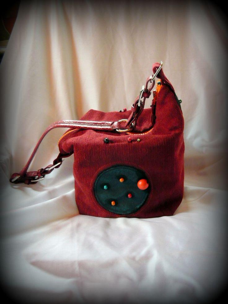 Kockatáska -Handmade by Judy Majoros: Ennek a kisméretű kockaformájú táskának bordó kordbársony bútorszövet a borítása. Fekete pöttyös tüllel borított fényes türkiz textilbőr pöttyök, valamint színes gyöngyök díszítik. Belseje bordó viszkózzal bélelt, gombokkal díszített, és két kisméretű rávarrt zseb található benne. Eleje és hátulja műanyag merevítést is kapott, így a táska üresen is tartja formáját. Pántja műbőr, fém csattal és karikával díszítve. tetején cipzárral záródik.