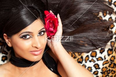 smiling young indian female with a rose in her hair. - Smiling young Indian female with a rose in her hair posing for the camera while lying on her back, Model: Stephanie Reddy