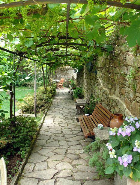 Arbor over cobblestone walkway, northwest Spain
