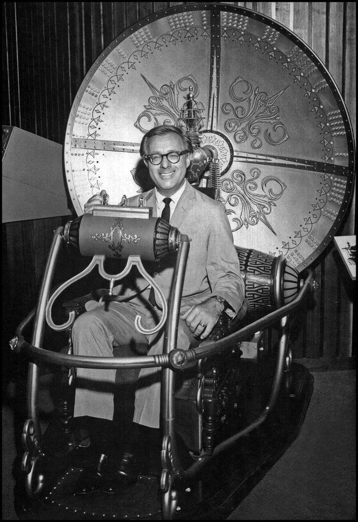 Ray Bradbury, sitting in the original time machine from the classic film, ca. 1960