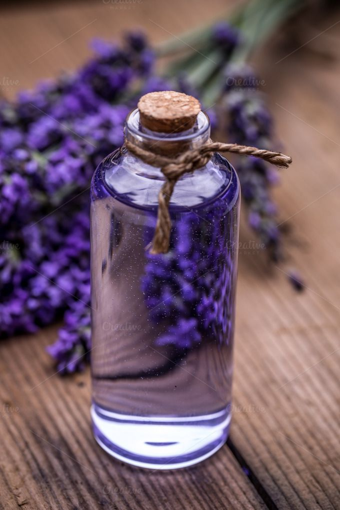Lavender oil in a glass bottle by Grafvision photography on @creativemarket