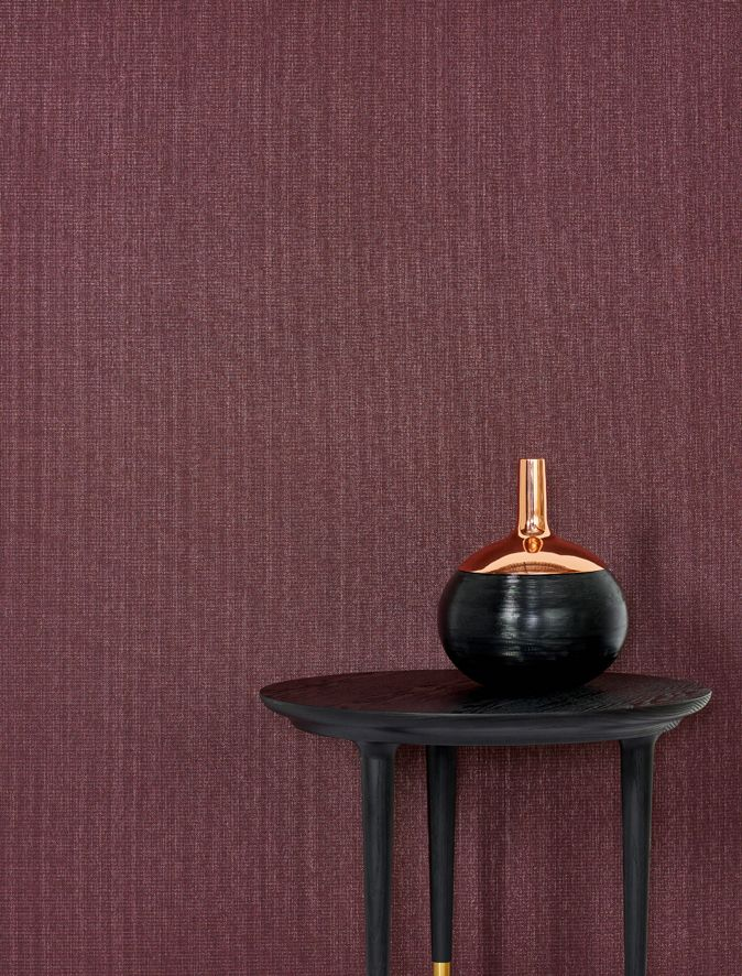 Luxe and shimmering, St Tropez from the Metallic Wallcoverings collection features an eye-catching weave of gold and silver threads. Pictured here in colour Fer, this beautiful deep burgundy wine tone emulates rich marsala next to Own World's side table and Tom Dixon's vessel/vase.