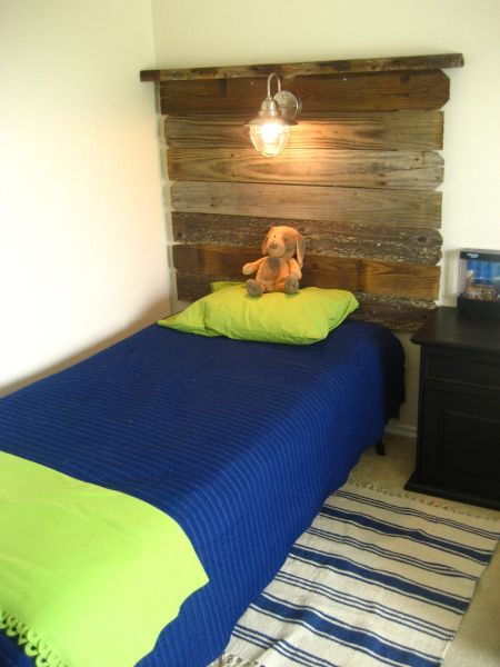 from the blog addicted2decorating, a boys room headboard made from aged wood and an outdoor light for a great reading light.