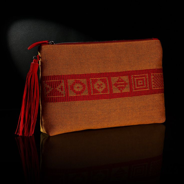 Τhe handmade woven envelope adorns patterns from Greek history and tradition. The background is in saffron color and the embroidery in bordeaux color.