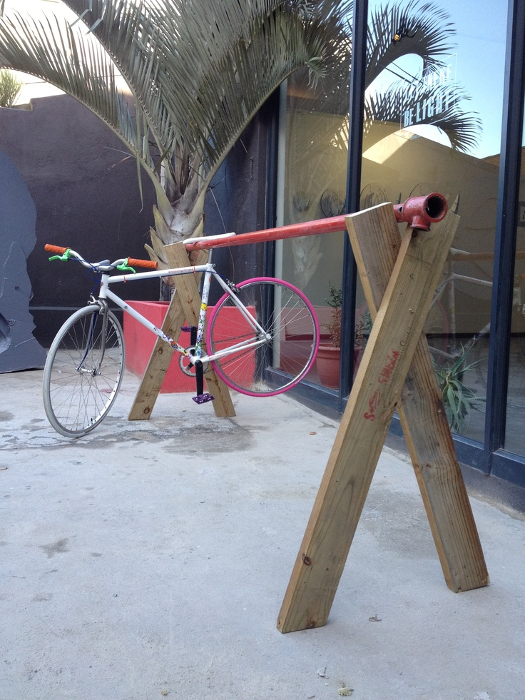 Old pipe and leftover wood makes up for a very cheap and cool bicycle rack