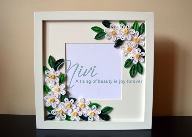 Photo frame with quilled flowers.