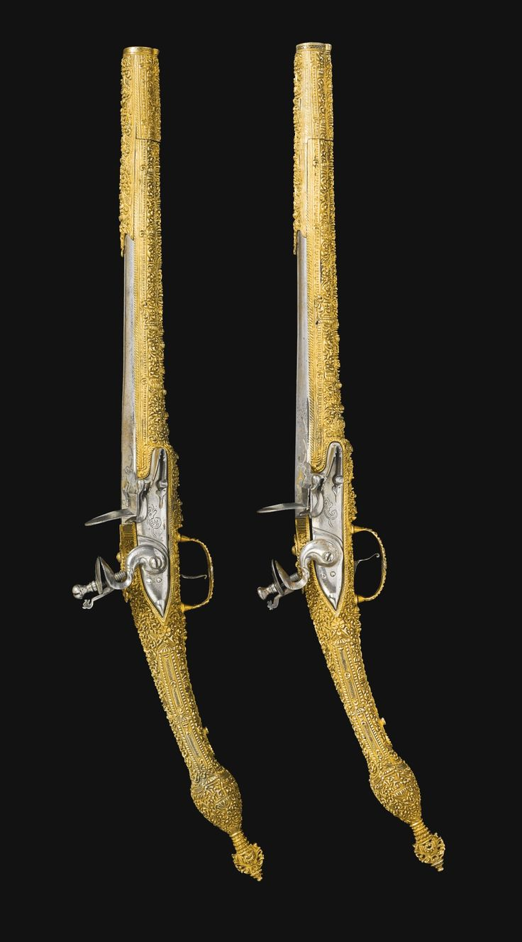 A FINE PAIR OF OTTOMAN FLINTLOCK SILVER-GILT EPIROT PISTOLS, IOANNINA, GREECE, 19TH CENTURY with long tapered steel barrels encased at the muzzle, the stocks decorated throughout with gilt-silver finely chiselled and chased with dense floral and scroll-designs, the grips with embossed palmette finials