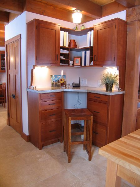A small nook serves as a desk area with ample workspace, illuminated by undercabinet lighting. A stool tucks easily under the marble counter, keeping the walkway open.
