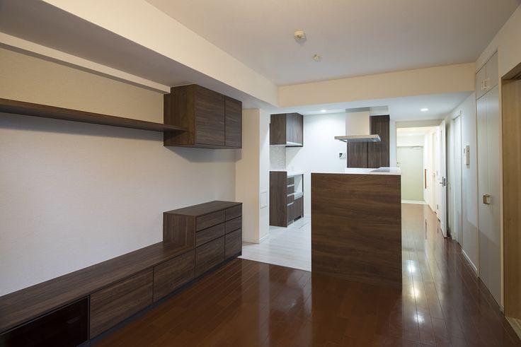 既存のフローリングに調和するウォルナット柄のキッチンや建具が白壁にシックに映える、シンプルモダンな空間。|リフォーム|キッチン|自然素材|壁面収納|