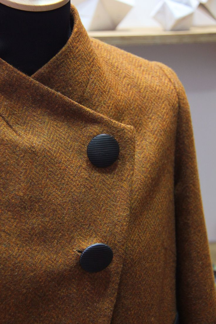 minimal style jacket, with two buttons, in a warm orange color on a herringbone pattern fabric