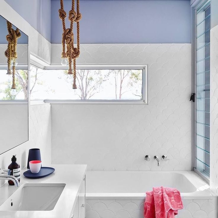 Purple and white contemporary bathroom features a purple walls half covered in white fish scale bathroom tiles continuing down to cover a bathtub finished with a polished nickel tub filler positioned under a wraparound window.