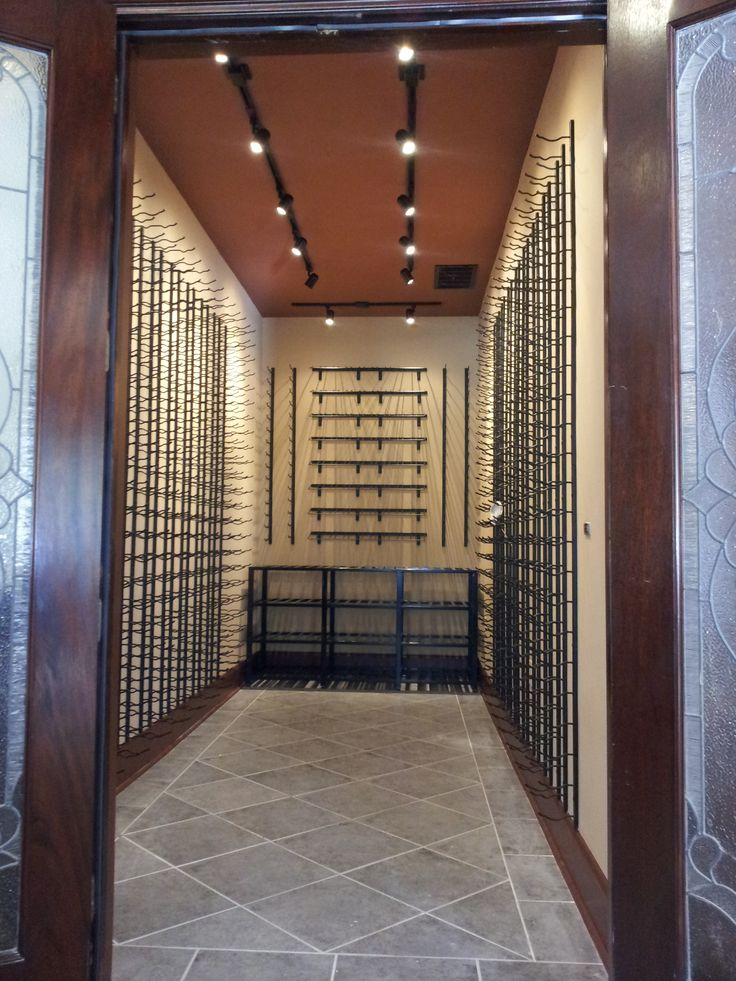 As this was to be a very modern contemporary style wine room we installed base moldings to the walls and matching floor trims with led track lighting on the ceiling. For the wine racks we chose Vintage View black finish metal racking. Click here to see more of this project http://www.winecellarspec.com/wine-cellar-builders-atlanta-project-custom-wine-cellars-conversion/#.