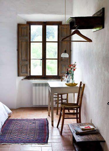 Beautiful deep set windows, indoor shutters, plaster-style windows, ethnic rug, simple wooden table and chairs, ovehead coat rack/shelf