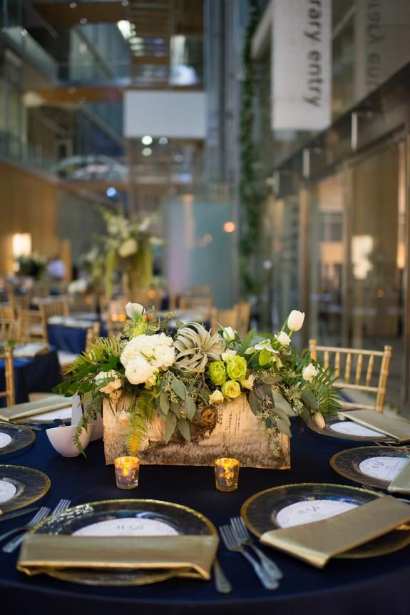 Mesmerizing Midnight Blue and Gold Wedding, Minneapolis Central Library - Linen Effects Wedding, Party, and Event Rental Decor - www.lineneffects.com - Photo by Jessica Ranae Photography |  Navy Satin tablecloths, glass with gold edge charger plates, gold foil napkins, gold chiavari chairs, and a low floral centerpiece in a birch box with lots of greenery and white flowers.