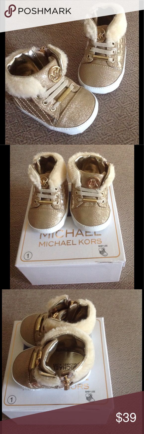 Michael Kors baby shoes. SZ 1 (3wks-6mo). NWOT Adorable MK gold baby shoes in gold. New in box/never worn. There is a tear in the clear plastic on top of box as shown in photo. Great gift! Michael Kors Shoes Sneakers