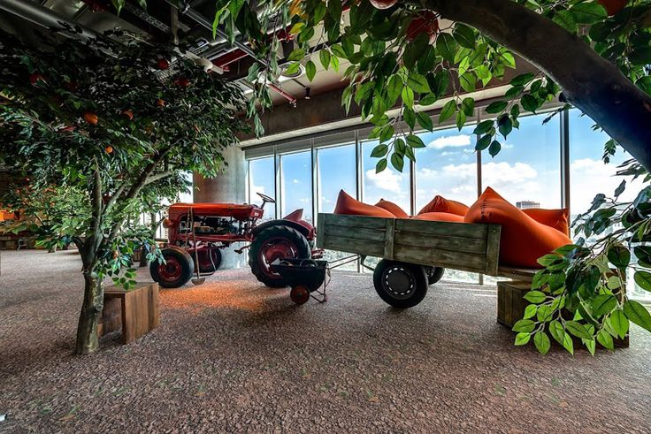 what an interesting and extraordinary idea for the office?! village style decorated place with a real tractor in the office