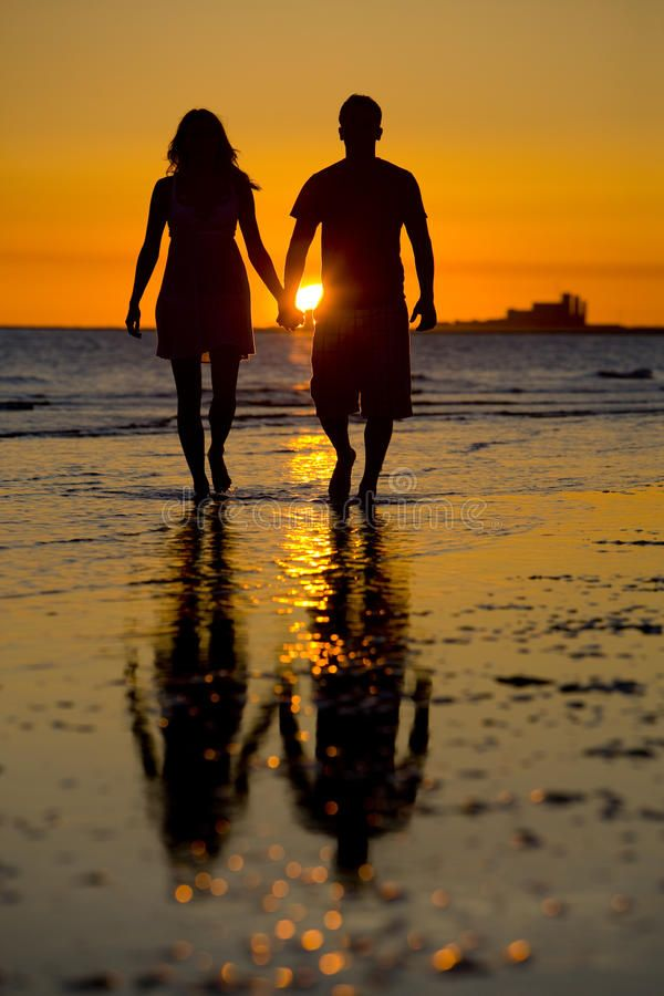 Silhouette Of Love Two Lovers Holding Hands On The Beach