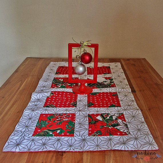 A decorative patchwork table runner. Bring a Christmas atmosphere to your home thanks to its festive colors. Also, the designs of the fabrics, such as the poinsettia, holly and pine, contribute to a perfect decoration for Christmas.  • SIZE | 77x43cm / 30.3 x 16.9 inches • FABRIC | 100% Cotton • COLOURS | green, red, white and gold. Back is red with tiny white dots. • 100% hand made • The tablerunner is washable at 30 degrees.  This product is unique, but if you want a similar one or you...