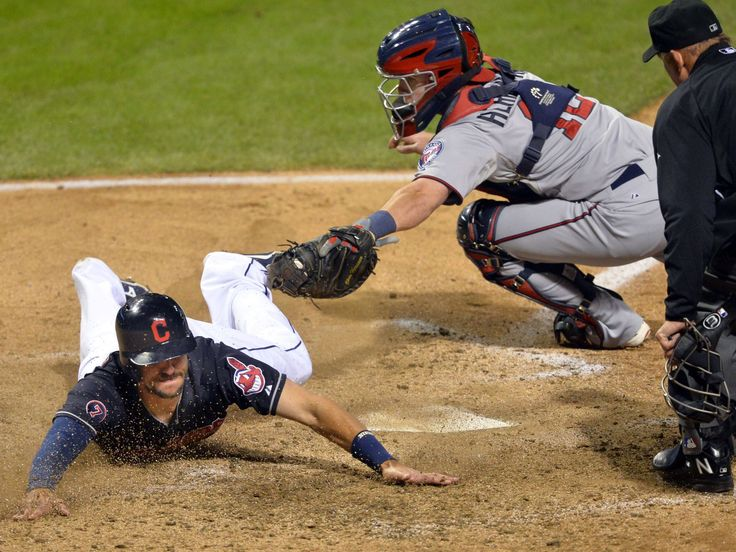 Cleveland Indians right fielder Lonnie Chisenhall, left, scores a run before a tag by Minnesota Twins catcher Chris Herrmann in the third inning at Progressive Field in Cleveland.  David Richard, USA TODAY Sports