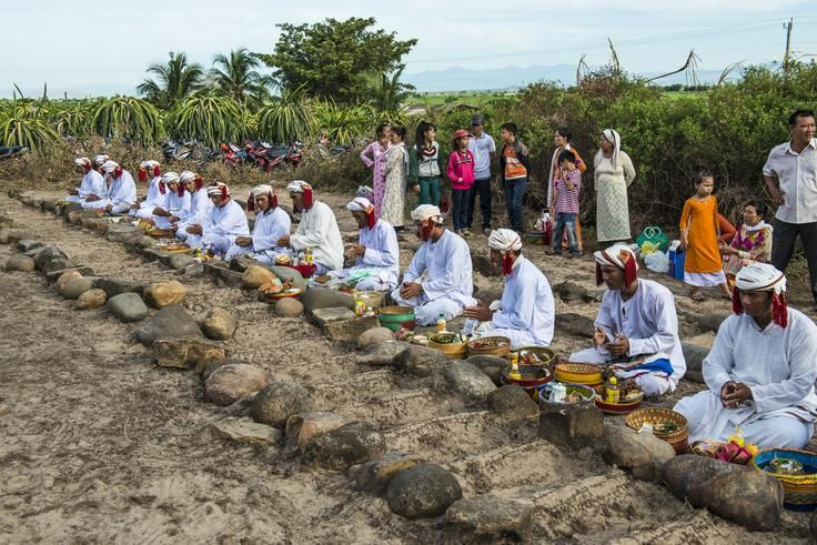 The Chams Muslim celebrating their Ramawan festival - the first day of Ramadan month - at sanctuary land. In that day, people visit their ancestors grave in early morning with the Muslim priests. In the picture, the Muslim priests sitting beside the tombs indicated by the rocks at two ends of the plough, praying and offering gifts in the bamboo basket to ancestors.