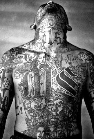 An MS-13 gang member bares his tattoos inside the Chelatenango prison. Foto: Moises Saman