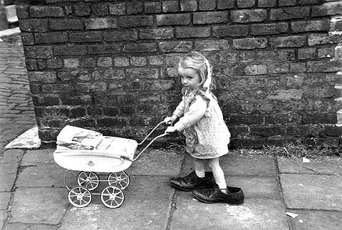 Little girl with her dad's shoes on.