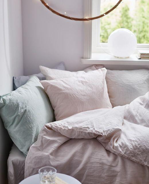 Close‑up van knus bed met handgeverfd beddengoed in pastelkleuren
