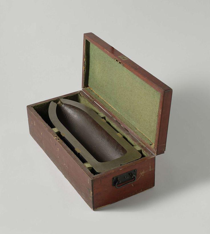 William Armstrong & Co. | 23 cm Granaat in houten kist, William Armstrong & Co., 1868 | Een halve overlangs doormidden gezaagde puntvormige 23 cm granaat, in een houten kist. De granaat is 67.3 cm lang en heeft een kaliber van 227 mm. Hij heeft twee ringen ingeperste nokken voor een getrokken loop met zes trekkende velden en is hol; in de neus een buisgat. Bovenaan zijn ondiepe gaten voor de munitie-kraan aangebracht.
