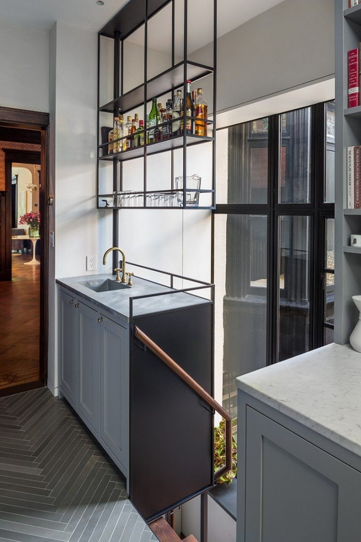 he shelving above the bar is blackened steel, and the bar counter and integral sink are made of zinc.