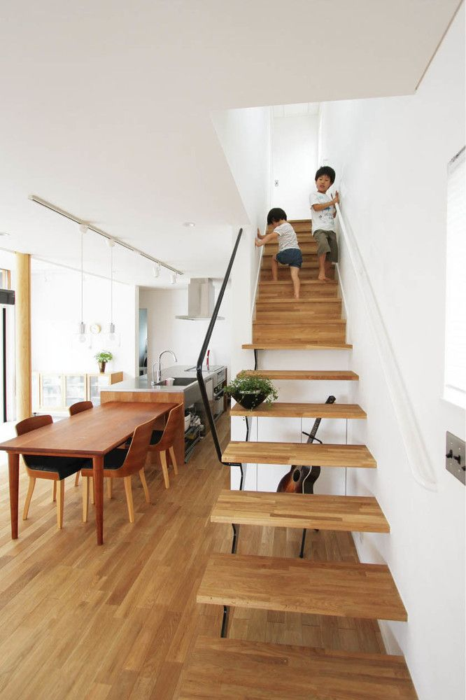 土間リビングの家(筑西の家)  敷地は、筑西市の中心市街地、歴史的な建築物も近隣に建ち並ぶ住宅地に位置します。 若いご夫婦と二人の子供達のための家。 1階と2階は吹き抜けにより繋がり、動線突き当たりの落ち着いた位置にある主寝室は、L字に張り出した形状とすることで、リビングと視線が重なる位置関係となっています。一体的な空間で構成することにより、互いの気配を感じることが出来る家、意外と短い家族全員で過ごす時間を、みんなで共有できるプランとしています。各部屋はプライバシーや空調効率を調整出来るよう、常時開放可能な開口でエリア分けされており、家族の成長に合わせ変化できるよう考えています。 LDKとひと繋がりになった広い土間は、縁側のように内外の境界を曖昧にし、積極的に人を招き入れる、開けた交流の場所をつくり出します。 深い軒や色彩など、現代的にアレンジした和のデザインにより、歴史ある街並みや地域の生活に溶け込み、永く愛され住み継がれて行く家になるよう設計しました。