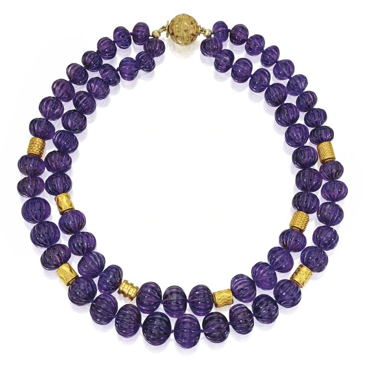 18 KARAT GOLD AND AMETHYST NECKLACE, BULGARI. The double-strand necklace composed of 67 fluted amethyst beads measuring approximately 18.8 to 11.9 mm, spaced by nine textured gold beads and a spherical clasp, length approximately 18½ inches, signed Bulgari.