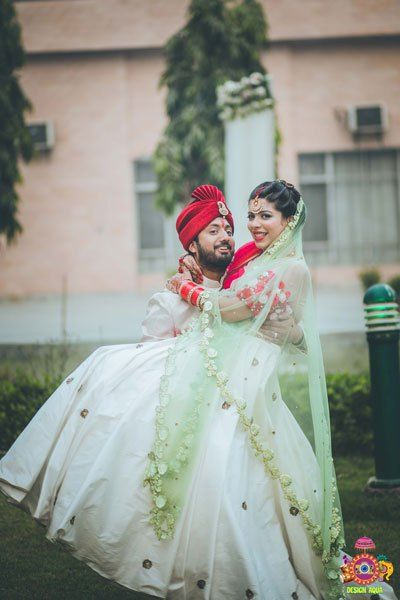 Chitrakshi and Neil | Offbeat wedding in Delhi | Day wedding full of ideas | Indian bride wearing an ivory lehenga with a floral sleeve blouse and a red and pista pastel double dupatta | Indian bride with a red sweetheart blouse with red white and green 3d flower decoupage on the sleeves |  Indian bride and groom drinking beer together | photo by Design Aqua | WIttyVows | indoor on the nose