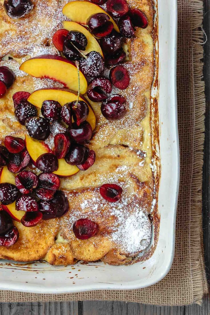 Stupid easy, and healthier, overnight baked French toast with challah bread, fresh fruit, and a side of honey simple syrup.