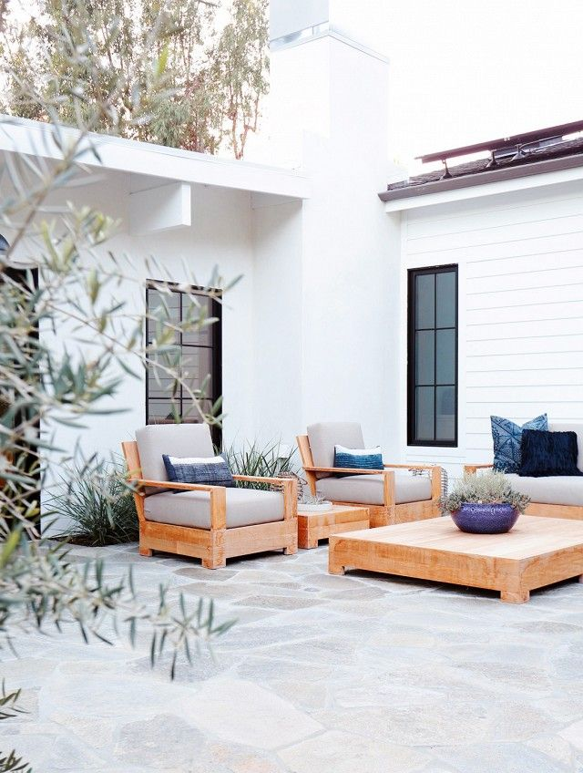 Tranquility and balance is the name of the game in this Malibu home's outdoor space. Light wood, stone-hued tones, and blues keep the peace.