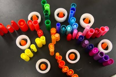 """Use marker lids, glue lids  tape spools to build structures  create designs ("""",)"""