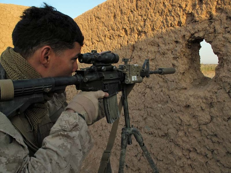 Lance Cpl. Paul Maxinoski, a scout sniper with 1st Battalion, 1st Marines, peers through the optic of M4 rifle with sound suppressor on a tripod in Trek Nawa, Afghanistan