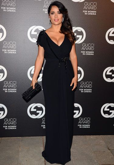 Beautiful dress, drapey material, showing skin with a low cut V neck, belted at waist.  Salma can carry off black.