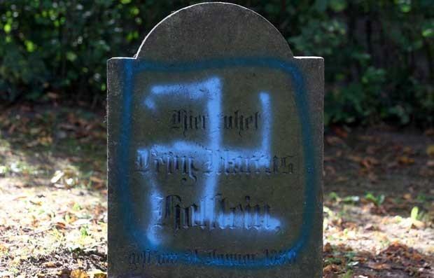 Suástica em lápide no cemitério judaico em Kroepelin, no nordeste da Alemanha, nesta terça-feira (4). Pessoas desconhecidas haviam contaminado o cemitério com cruzes suásticas e slogans nazistas no começo da segunda (2) (Foto: AFP)
