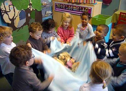 jeu avec un ourson et une couverture ou un parachute