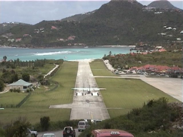 Airplane arriving at St. Barth Airport, the landing strip ends at the beach at St. Jean