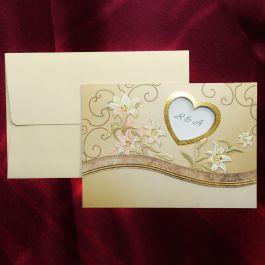 Invitatia este compusa din trei parti. Partea de deasupra textului invitatiei are la baza doua elemente: partea de jos este crem, simpla si este unita de partea de sus prin intermediul unei benzi curbate maro cu accente aurii. In partea de sus observam elemente decorative, florale si o inimioare decupata prin care se vad initialele mirilor. Plicul, crem, este inclus in pret.  #invitatie de #nunta #mirese #miri #invitatii #elegante #originale