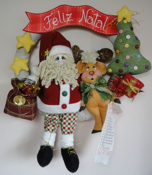 """Guirlanda Papai Noel, Rena e os Desejos de Natal.  A Rena do Papai Noel carrega uma listinha com os seus desejos de Natal: """"paz, amor, luz, alegria, saúde, prosperidade, abundância, felicidade, inspiração, fé, harmonia, fé, bênçãos.""""  Tamanho aproximado: 43 cm (largura) x 50 cm (altura). R$ 165,00"""