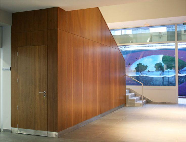 Mampara realizada con estructura interna de madera acabada con tableros de madera natural de Iroco y puerta integrada en el conjunto.