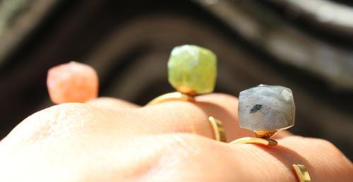 Ringe med cubes  Til disse ringe er der brugt følgende materialer:  3 stk. fingerring med stift og skål, forgyldt stål el. mat forgyldt stål 1 stk. cube i rød solsten 1 stk. cube i vesuvianit 1 stk. cube i labradorit, mørkegrå 3 stk. headpin med plade i forgyldt sterlingsølv + bidtang + lim  ringe med firkantet halvædelsten  Da disse cubes er gennemboret, er der limet et lille stykke headpin med plade i perlen så hullet ikke ses. Brug en bidtang til at klippe noget af
