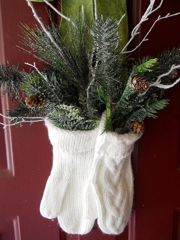 des branches de pin décorées de neige artificielle mises dans deux gants en tricot