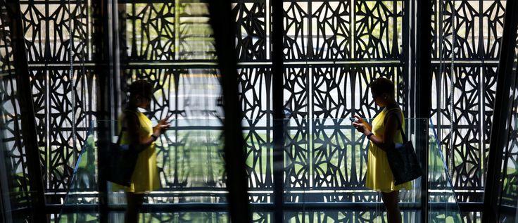 Reflejada en el vidrio, una mujer se pone delante de los paneles de detección de metales que componen la corona ?? ??  que encierra el Museo Nacional de Historia Afroamericana y Cultura en el National Mall en Washington el 14 de de septiembre de 2016.