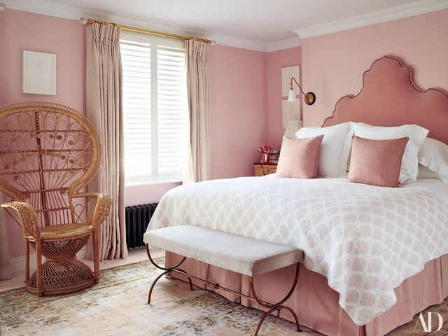 A rose-pink linen from Fromental covers the walls of the master bedroom. Vintage peacock chair; headboard by Ensemblier in a mohair velvet by Claremont; Quilt from Oka; Bed linens from the White Co.