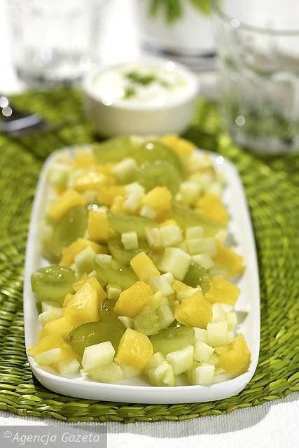 Zrób sos z jogurtu, soku z limonki, miodu i skórki cytrynowej. Przykryj i wstaw do lodówki. Ćwiartkę ananasa obierz, miąższ pokrój na kawałeczki. Wszystkie owoce wymieszaj w misce, przykryj i wstaw do lodówki. Jeśli chcesz, możesz posypać je odrobiną cukru pudru do smaku. Po 3-6 godzinach wyjmij z lodówki owoce i sos jogurtowy, wymieszaj, odłóż na 15 minut, aby smaki się połączyły. Do sałatki możesz dodać różne miękkie owoce sezonowe: truskawki, poziomki, jagody, porzeczki, maliny, morele…