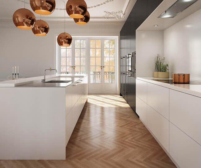 Liker det strenge kjøkkenet til det klassiske fiskebensmønstrede gulvet og varmen fra treverket som også er i belysningen.